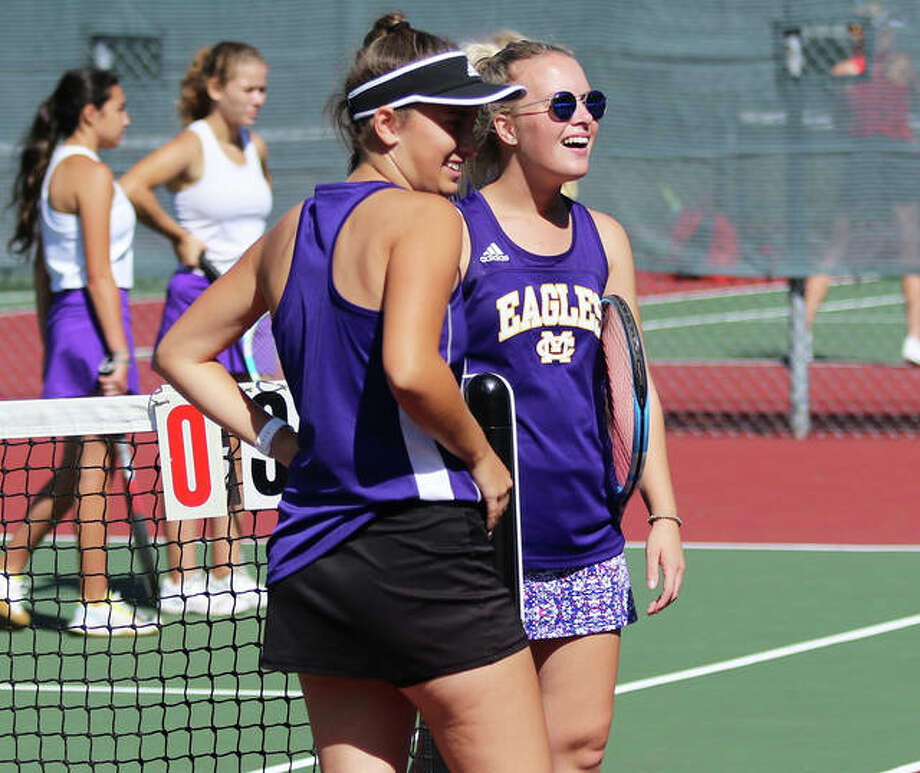 Civic Memorial's No. 1 doubles team Kennedy Loewen (right) and Hannah Butkovich share a laugh with coach Matt Carmody (not pictured) on Saturday morning during a break in play after taking a 3-0 lead in their match with Collinsville in Alton's Robert Logan Invitational girls tennis tournament in Troy. The eight-team tourney was played on courts at Alton and Triad high schools. Triad defeated Jersey in the championship match. Photo: Greg Shashack / The Telegraph