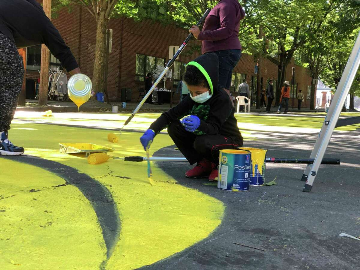 Resdents came together to paint a mural honoring Black Lives Matter on Bassett Street in New Haven Saturday. Here, Carmen Lawson-Fernandez, 7, helps out.