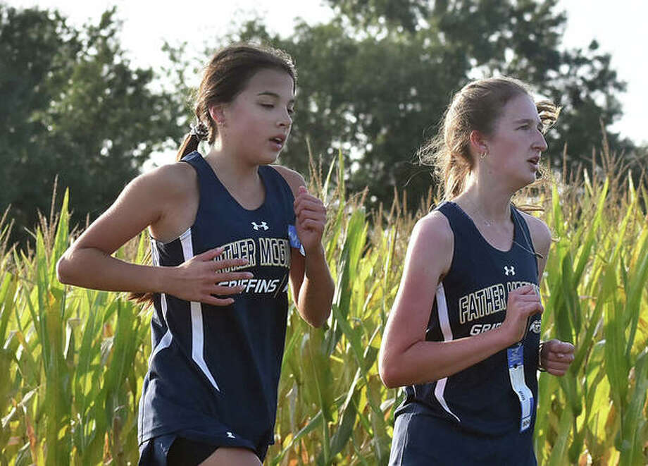 Father McGivney's Kaitlyn Hatley, left, and Alyssa Terhaar work together through the second mile at the Mascoutah Invitational on Saturday.