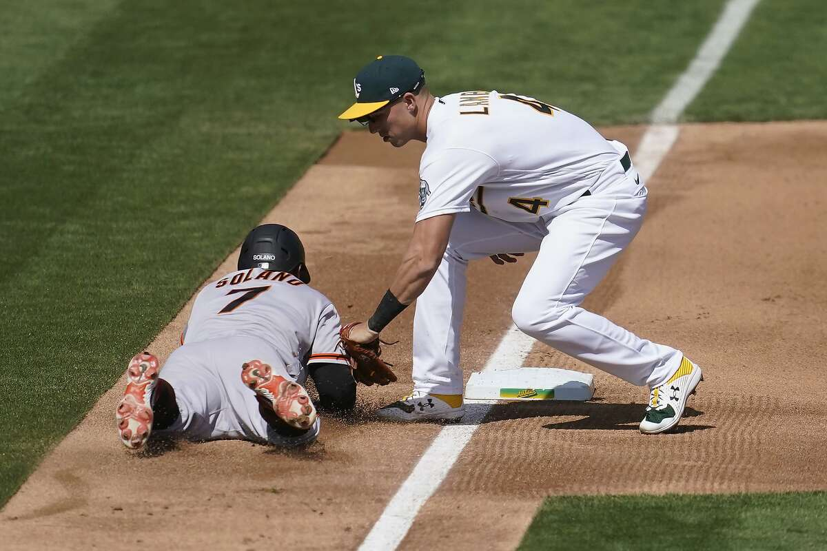 Oakland Athletics third baseman Jake Lamb, right, tags out San Francisco Giants' Donovan Solano during the fourth inning of a baseball game in Oakland, Calif., Saturday, Sept. 19, 2020. (AP Photo/Jeff Chiu)