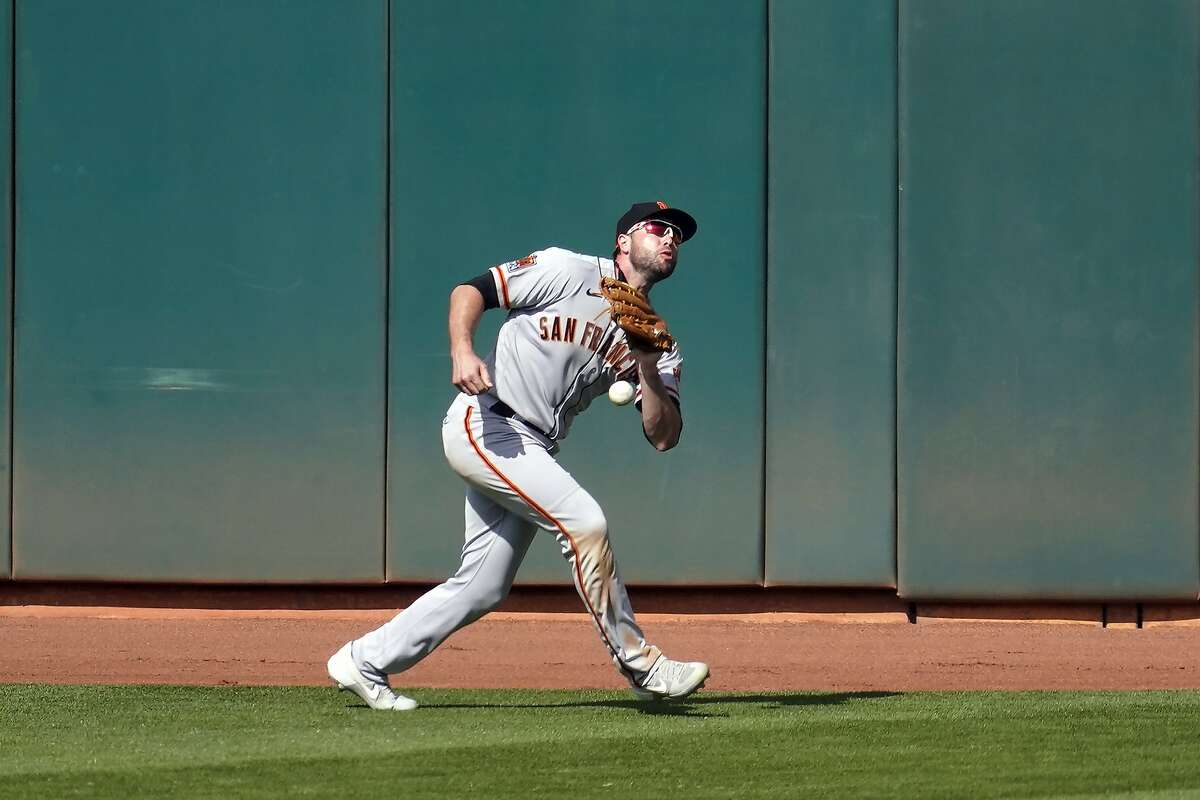 San Francisco Giants left fielder Darin Ruf drops a fly ball hit by Oakland Athletics' Ramon Laureano, who reached base on a fielder's choice, during the seventh inning of a baseball game in Oakland, Calif., Saturday, Sept. 19, 2020. (AP Photo/Jeff Chiu)