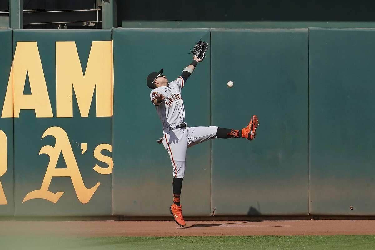 San Francisco Giants center fielder Mauricio Dubon cannot catch a two-run triple hit by Oakland Athletics' Tommy La Stella during the seventh inning of a baseball game in Oakland, Calif., Saturday, Sept. 19, 2020. (AP Photo/Jeff Chiu)