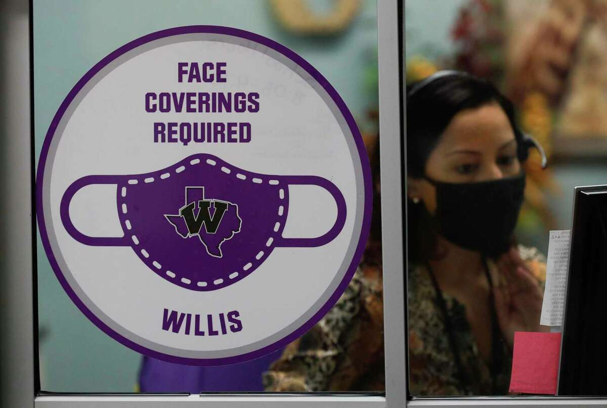 A sign outside the window of receptionist Lisa Cantarero's window reminds visitors that face masks are required at William Loyd Meador Elementary School, Thursday, Sept. 10, 2020, in Willis. Students at Willis ISD returned to in-person school on Tuesday, Sept. 8.