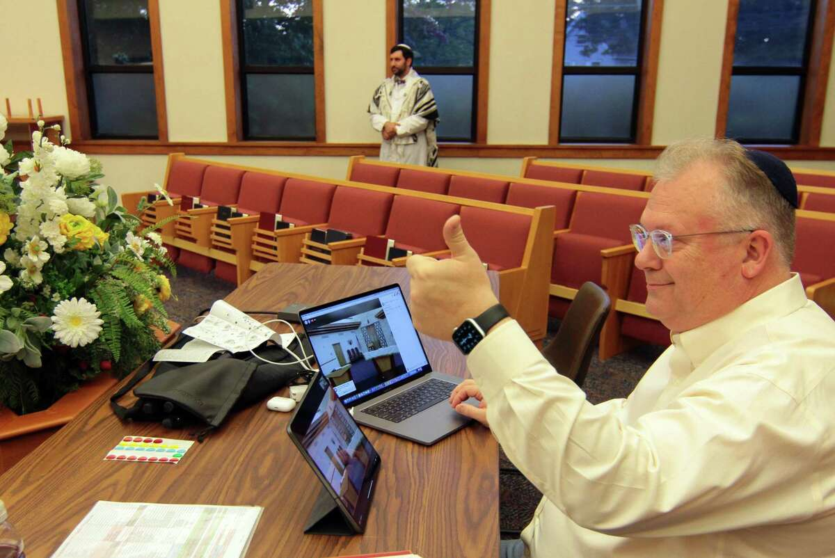 Congregation B'nai Torah's Fred Knopf gives the thumbs up signal to Rabbi Colin Brodie to start the Rosh Hashanah holiday service via livestream in Trumbull on Friday.
