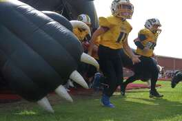 The Deer Park Senior Tigers rush out of their inflatable mascot Saturday afternoon at Bubba McLean Stadium.