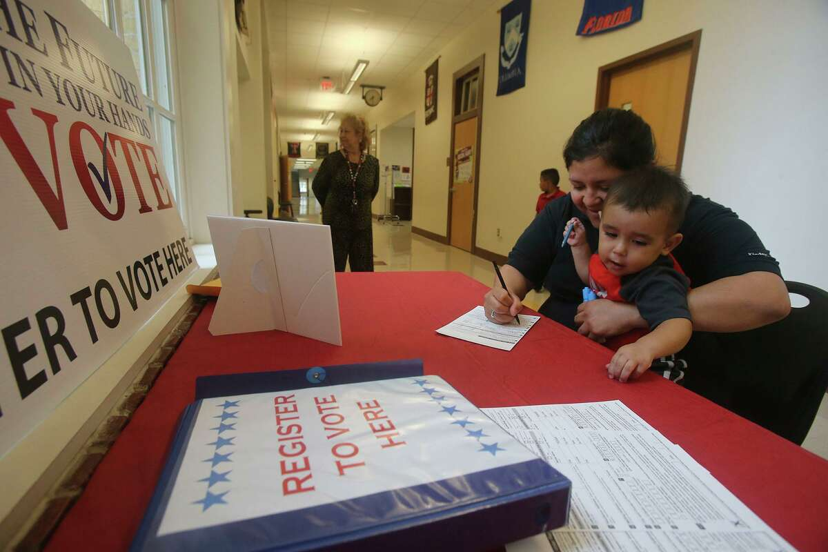 Juanita Vargas, right, holds her son Viggo Vargas, 18 months, while she fills out a voter registration card at Hawthorne Academy in 2016. Tuesday is National Voter Registration Day, and the League of Women Voters of the San Antonio Area are hosting a drive-up voter registration event at the Pearl.