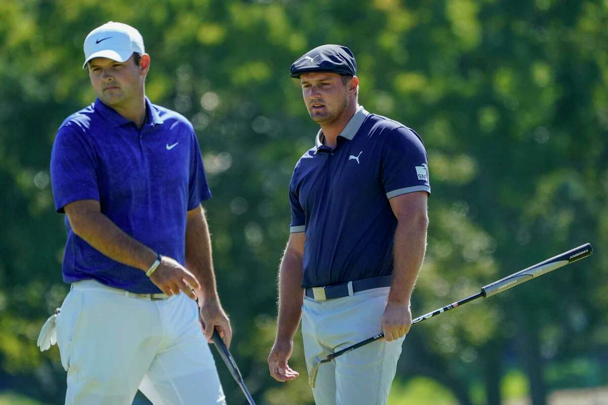 Patrick Reed, of the United States, and Bryson DeChambeau, of the United States, prepare to putt on the first green during the third round of the US Open Golf Championship, Saturday, Sept. 19, 2020, in Mamaroneck, N.Y. (AP Photo/Charles Krupa)