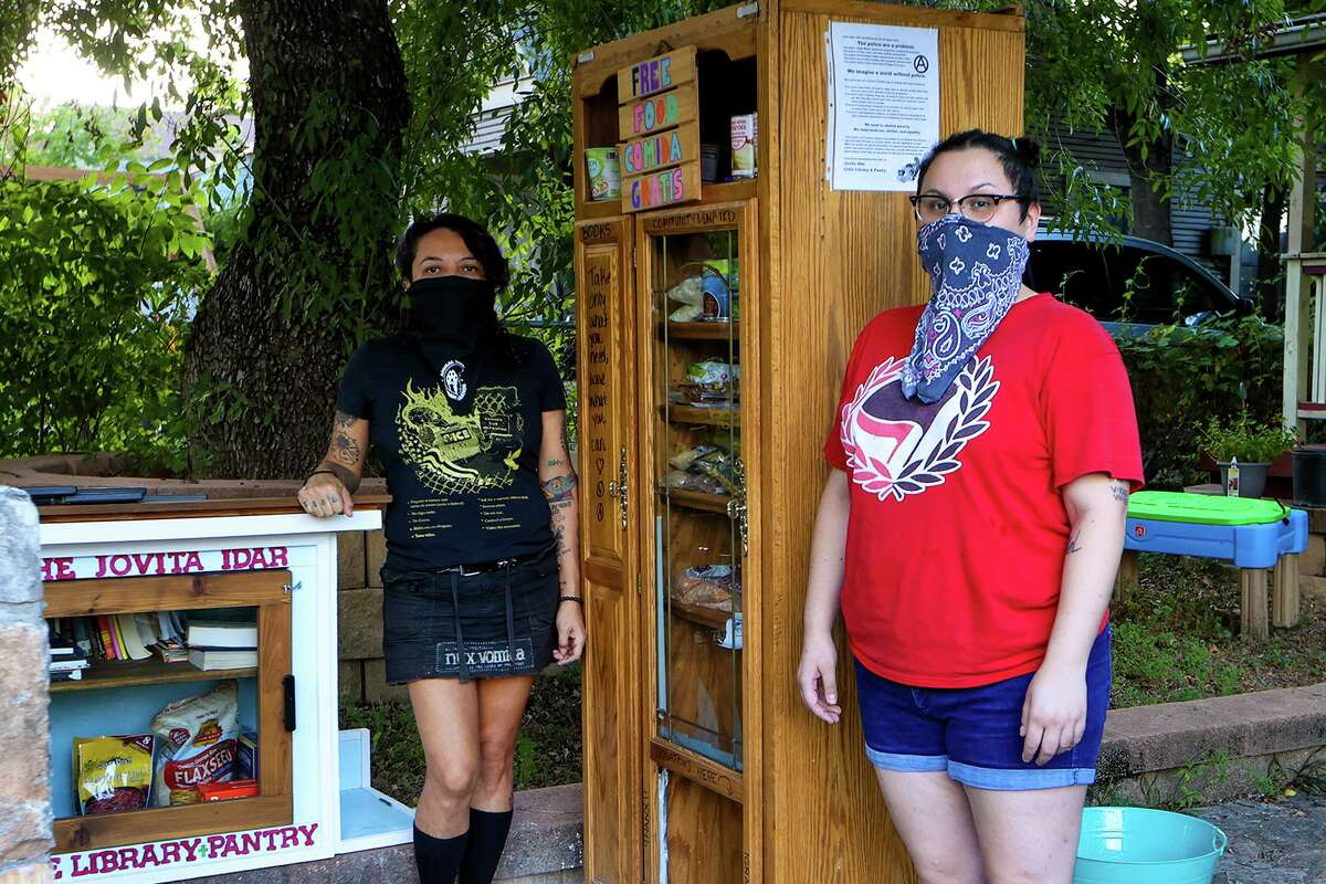 Ale Tierra, left, and Krys Sustaita at the Jovita Idár Little Library & Pantry on Tuesday, Sept. 15, 2020. The vegan and vegetarian pantry at 1527 San Francisco provides food, books, and DVDs to anyone in need 24/7. Sustaita and Tierra opened the free pantry in the first week of August and will soon be opening their second location in front of Viva Vegeria at 1422 Nogalitos.
