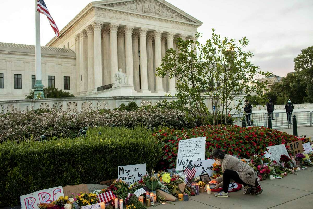 A mourner lights a candle at a makeshift memorial outside the Supreme Court building in Washington, on Saturday, Sept. 19, 2020, following the death of Justice Ruth Bader Ginsburg a day earlier. (Jason Andrew/The New York Times)