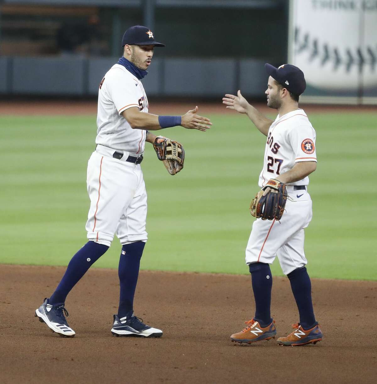 Houston Astros Carlos Correa (1) and Jose Altuve (27) celebrate the Astros 3-2 win over the Arizona Diamondbacks after the ninth inning of an MLB baseball game at Minute Maid Park, Saturday, September 19, 2020, in Houston.