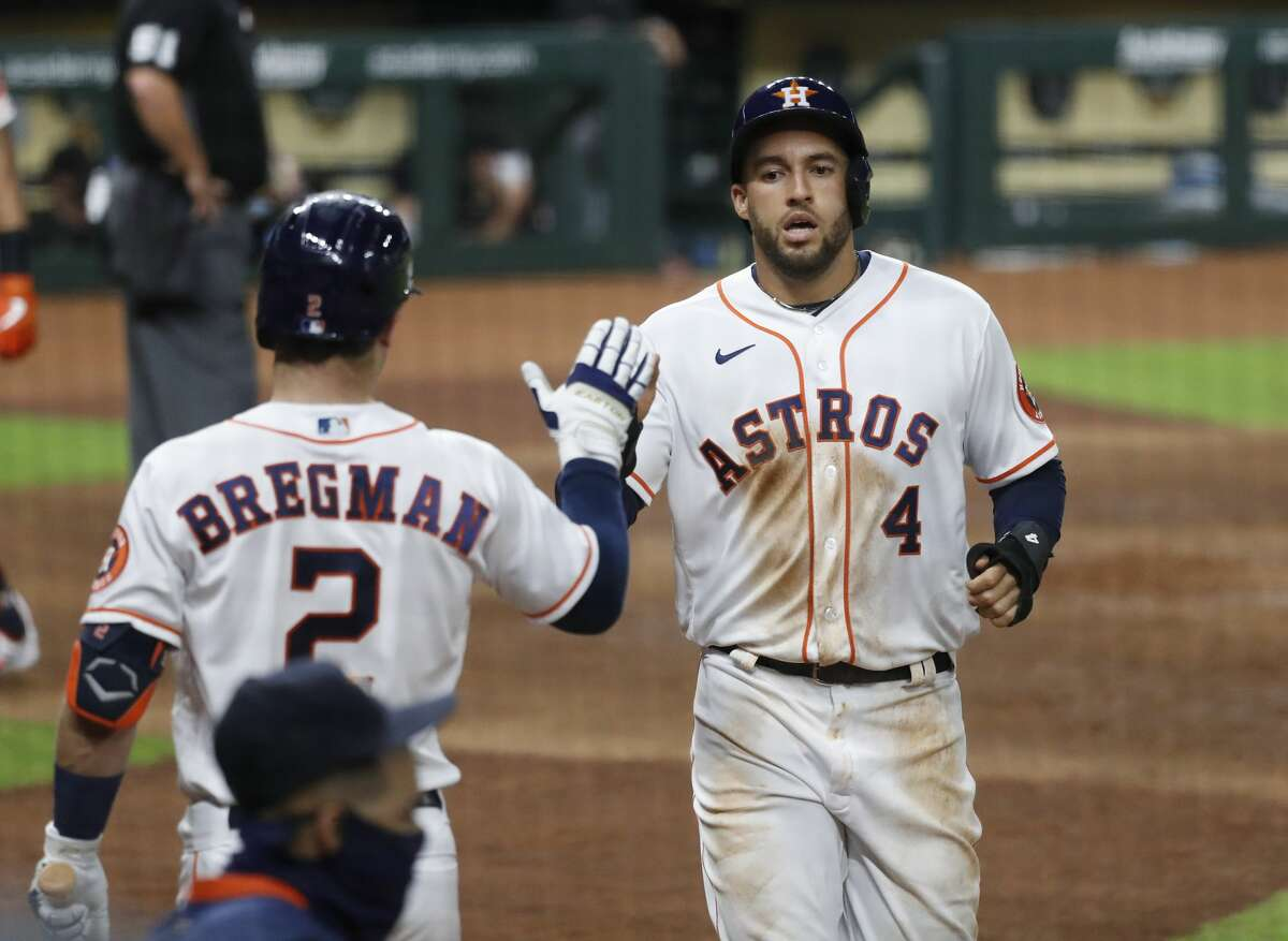 Houston Astros George Springer (4) celebrates with Alex Bregman (2) after he scored a run on Jose Altuve's double during the sixth inning of an MLB baseball game at Minute Maid Park, Saturday, September 19, 2020, in Houston.