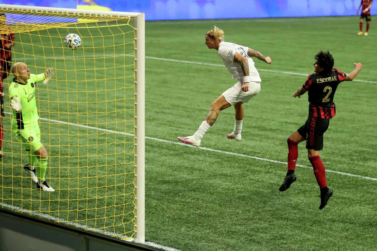 Miami defender Break Shea, center, heads a goal against Atlanta United goalkeeper Brad Guzan, left, and defender Franco Escobar, right, in the first half of an MLS match Saturday, Sept. 19, 2020, in Atlanta. (Jason Getz/Atlanta Journal-Constitution via AP)