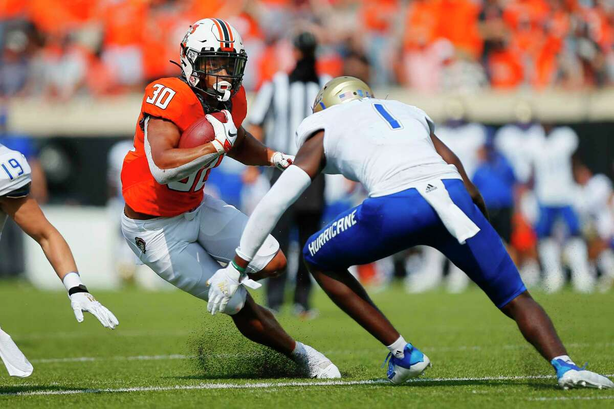 STILLWATER, OK - SEPTEMBER 19: Running back Chuba Hubbard #30 of the Oklahoma State Cowboys tries to make a cut against safety Kendarin Ray #1 of the Tulsa Golden Hurricanes in the third quarter on September 19, 2020 at Boone Pickens Stadium in Stillwater, Oklahoma. (Photo by Brian Bahr/Getty Images)