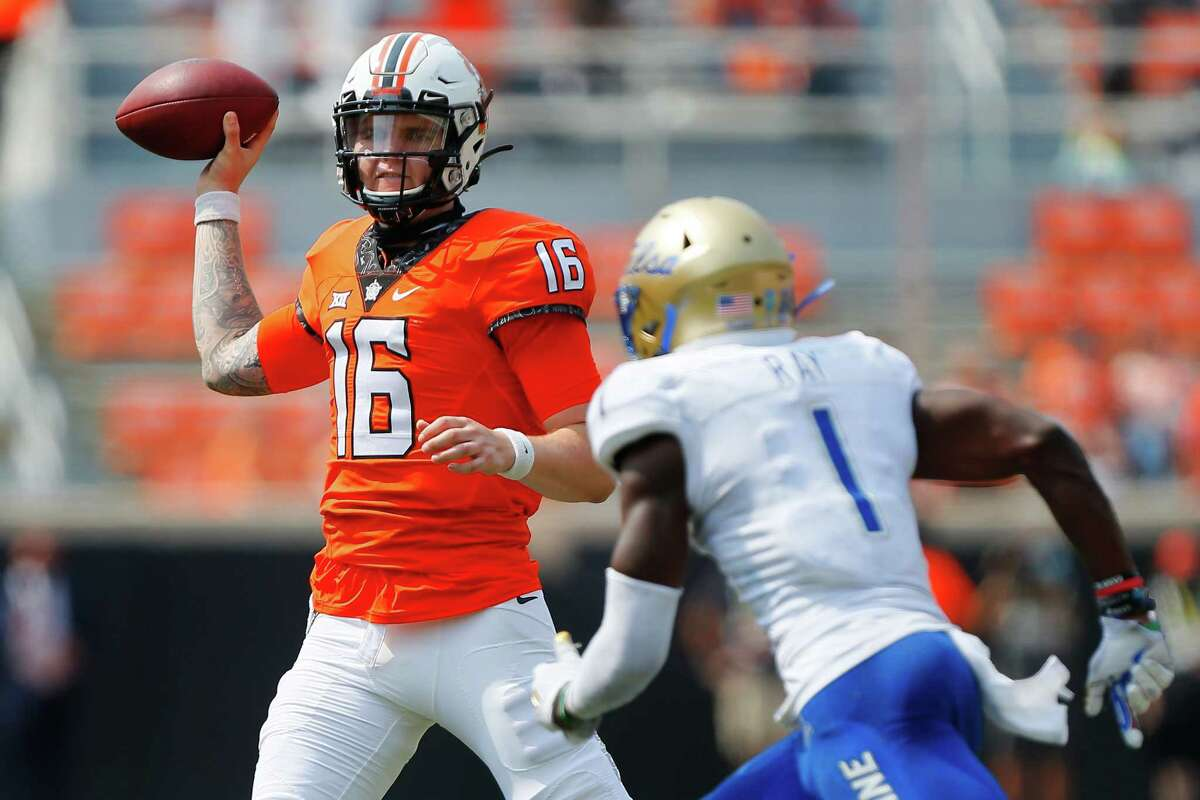 STILLWATER, OK - SEPTEMBER 19: Quarterback Shane Illingworth #16 of the Oklahoma State Cowboys rolls out as he looks for a receiver in the end zone under the defense of safety Kendarin Ray #1 of the Tulsa Golden Hurricanes in the fourth quarter on September 19, 2020 at Boone Pickens Stadium in Stillwater, Oklahoma. (Photo by Brian Bahr/Getty Images)