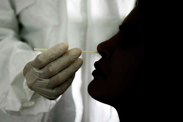 A doctor takes a nasal swab sample to test for COVID-19 at the Cocodrilos Sports Park in Caracas, Venezuela, Saturday, Sept. 19, 2020, amid the new coronavirus pandemic.