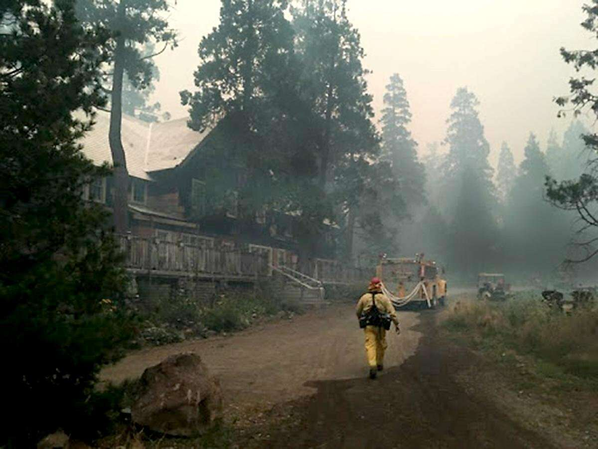 Firefighters walk past the lodge as they fight back the Breitenbush Hot Springs wildfires in Oregon. (Courtesy photos Breitenbush Hot Springs/TNS)
