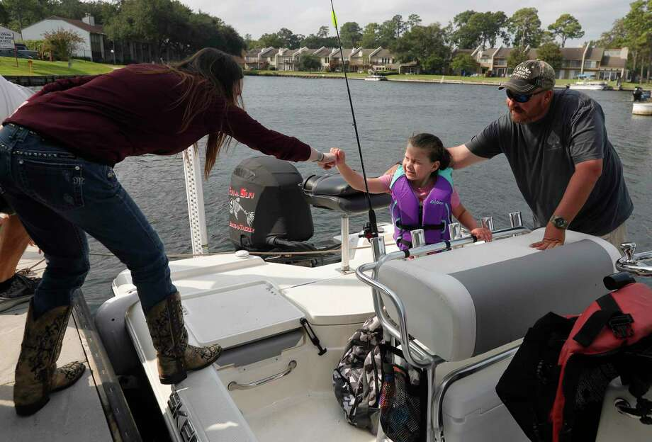 Danielle Sumrall, center, gets a fist-bump from Rachelle Slaughter beside her father, Mike, before heading out to fish on Lake Conroe as part of Casting for Casey, a free event for families with special needs children, Saturday, Sept. 19, 2020, in Montgomery. The event gave children the opportunity to go fishing with anglers on Lake Conroe. Photo: Jason Fochtman, Houston Chronicle / Staff Photographer / 2020 © Houston Chronicle