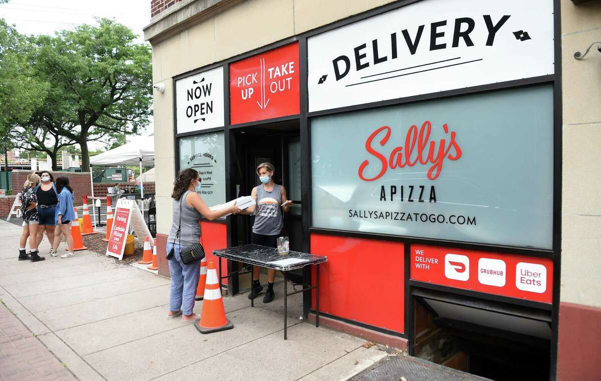 A customer gets a takeout order at Sally's Apizza on Wooster Street in New Haven on July 22, 2020.