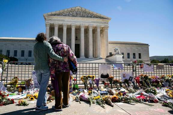 WASHINGTON, DC - SEPTEMBER 20: Women embrace at a makeshift memorial for late Supreme Court Justice Ruth Bader Ginsberg on the steps of the United States Supreme Court on September 20, 2020 in Washington, DC. Ginsberg passed away Friday night and is expected to be buried at Arlington National Cemetery later today. (Photo by Alex Edelman/Getty Images)