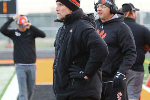Edwardsville coach Matt Martin (front) watches his team during last season's Class 8A second-round playoff game in Minooka.