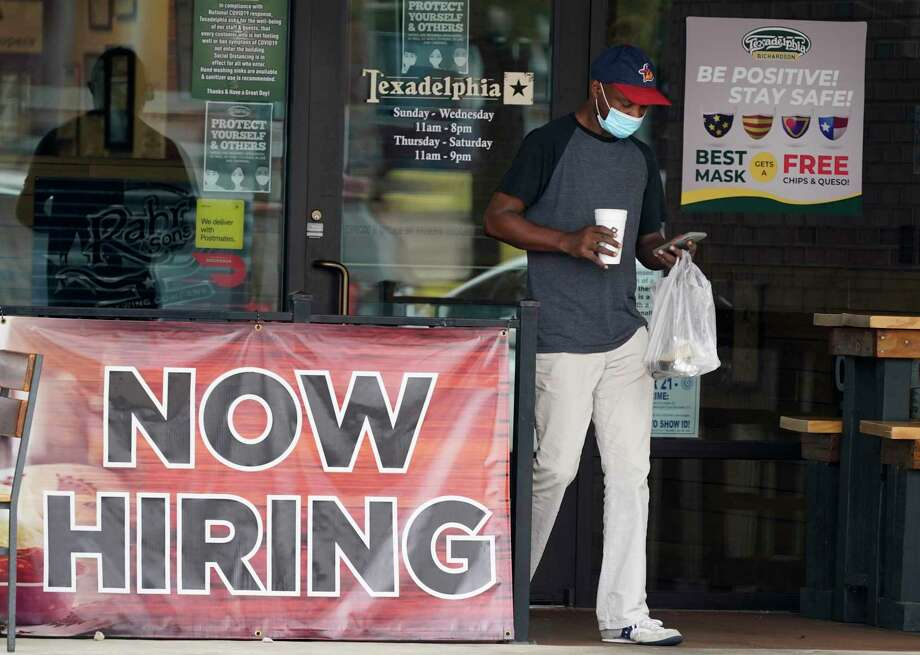A customer wears a mask and looks at their cell phone as they carry their order past a now hiring sign at an eatery in Richardson, Texas, Wednesday, Sept. 2, 2020. The U.S. unemployment rate fell sharply in August to 8.4% from 10.2% even as hiring slowed in August as employers added the fewest jobs since the pandemic began. (AP Photo/LM Otero) Photo: LM Otero, STF / Associated Press / Copyright 2020 The Associated Press. All rights reserved.