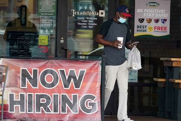 A customer wears a mask and looks at their cell phone as they carry their order past a now hiring sign at an eatery in Richardson, Texas, Wednesday, Sept. 2, 2020. The U.S. unemployment rate fell sharply in August to 8.4% from 10.2% even as hiring slowed in August as employers added the fewest jobs since the pandemic began. (AP Photo/LM Otero)