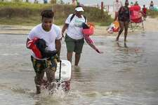 Tyler Heads totes his belongings through tidewaters as he and other beachgoers cross the flooding Stewart Beach parking lot in Galveston, Texas on Saturday, Sept. 19, 2020. Tropical Storm Beta continues to move through the Gulf of Mexico and is expected to bring tidal surge and heavy rain to the area. (Stuart Villanueva/The Galveston County Daily News via AP)