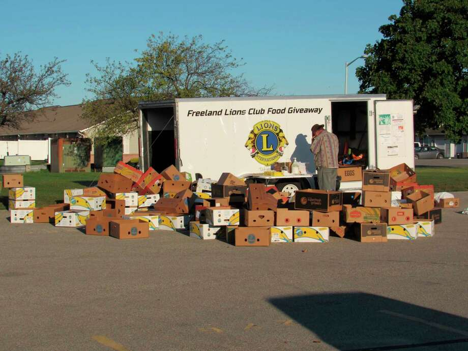 A volunteer helps unload boxes from the Freeland Lions Club's trailer on Saturday, Sept. 19. The club hosted its bi-monthly free food giveaway, serving about 300 packages to families. (Victoria Ritter/vritter@mdn.net)
