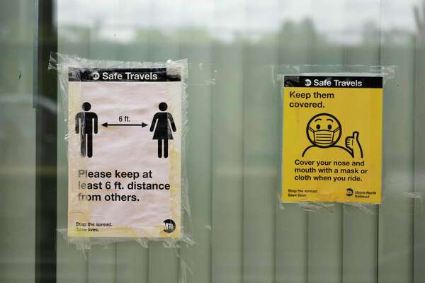 Signs promote social distancing and masks on the platform of the Metro-North station in downtown Greenwich, Conn. Monday, Sept. 14, 2020. Monday was the first day Metro-North began issuing $50 fines to passengers not wearing masks.
