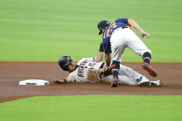 Arizona Diamondbacks Josh Rojas (10) is caught stealing second base by Houston Astros second baseman Jose Altuve (27) during the first inning of an MLB baseball game at Minute Maid Park, Sunday, September 20, 2020, in Houston.
