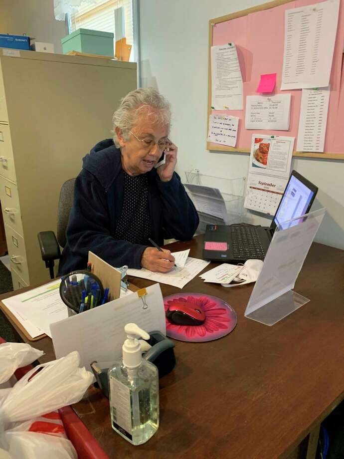 When not busy sorting bread, Sara Ham assists clients on the phone at Manna Pantry of Big Rapids, where she volunteers two days a week. (Submitted photo)