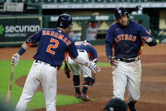 Houston Astros George Springer celebrates with Alex Bregman after his second home run of the day during the seventh inning of an MLB baseball game at Minute Maid Park, Sunday, September 20, 2020, in Houston. Springer's home run was the 2000th home run in Minute Maid Park.