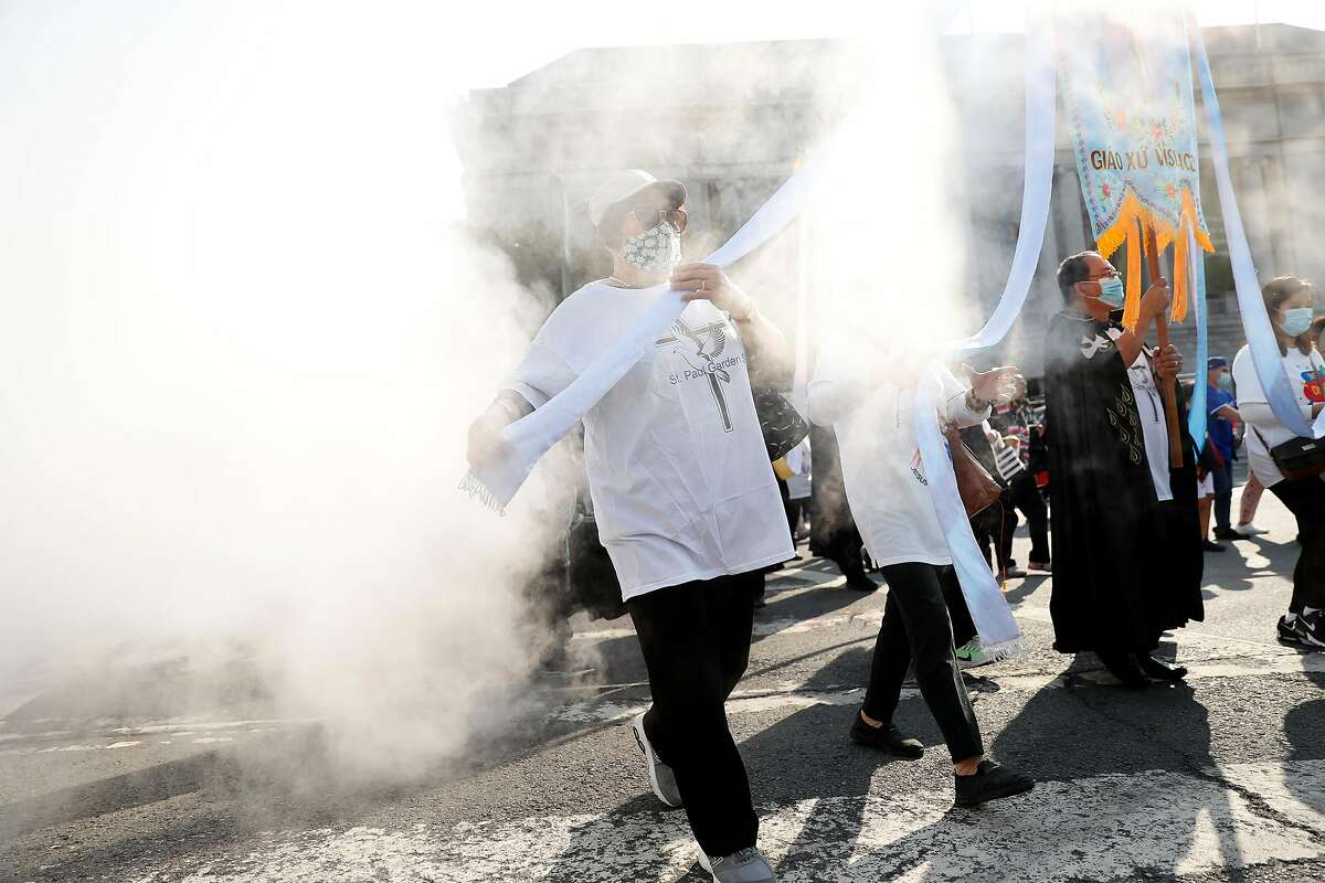 Catholic parishioners led by Archbishop Salvatore J. Cordileone pass through steam from a sewer grate while arriving at City Hall to process to St, Mary's Cathedral to protest against coronavirus restrictions in San Francisco, Calif., on Sunday, September 20, 2020.