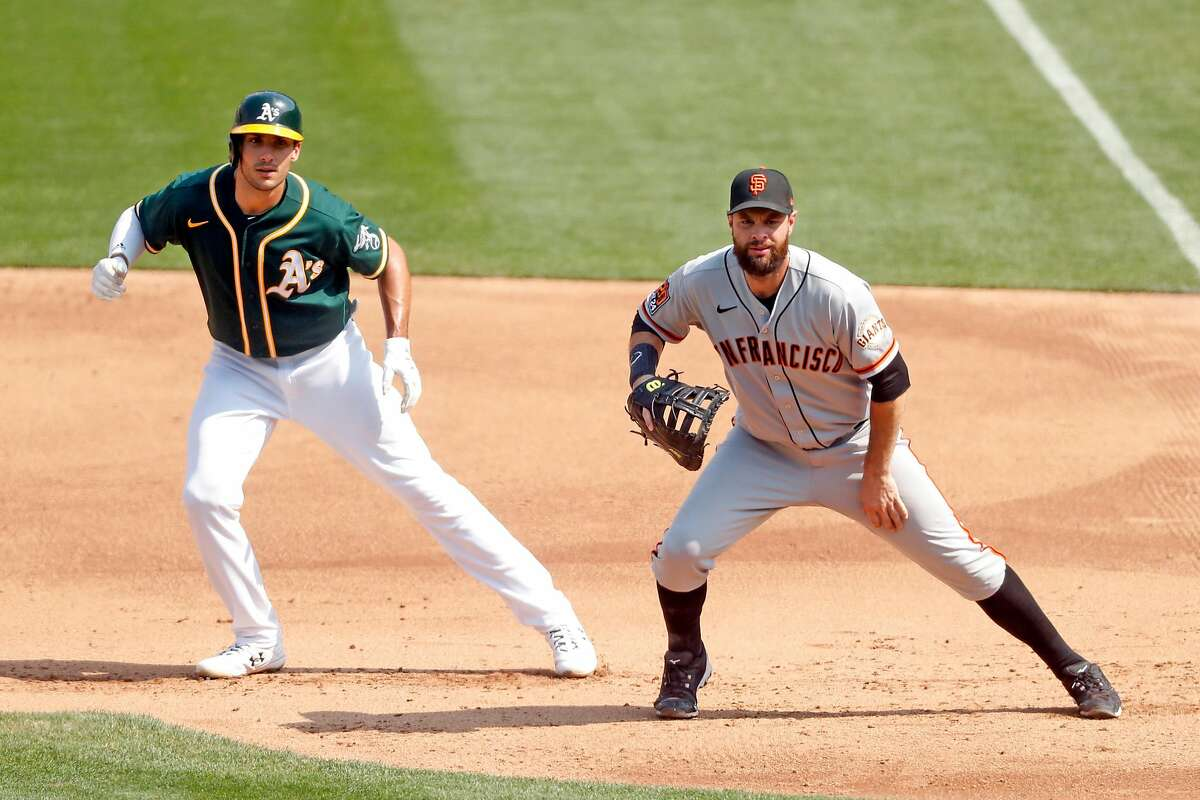Oakland Athletics' Matt Olson leads off as San Francisco Giants' Brandon Belt gets in defensive position in 4th inning in MLB game at Oakland Coliseum in Oakland, Calif., on Sunday, September 20, 2020.