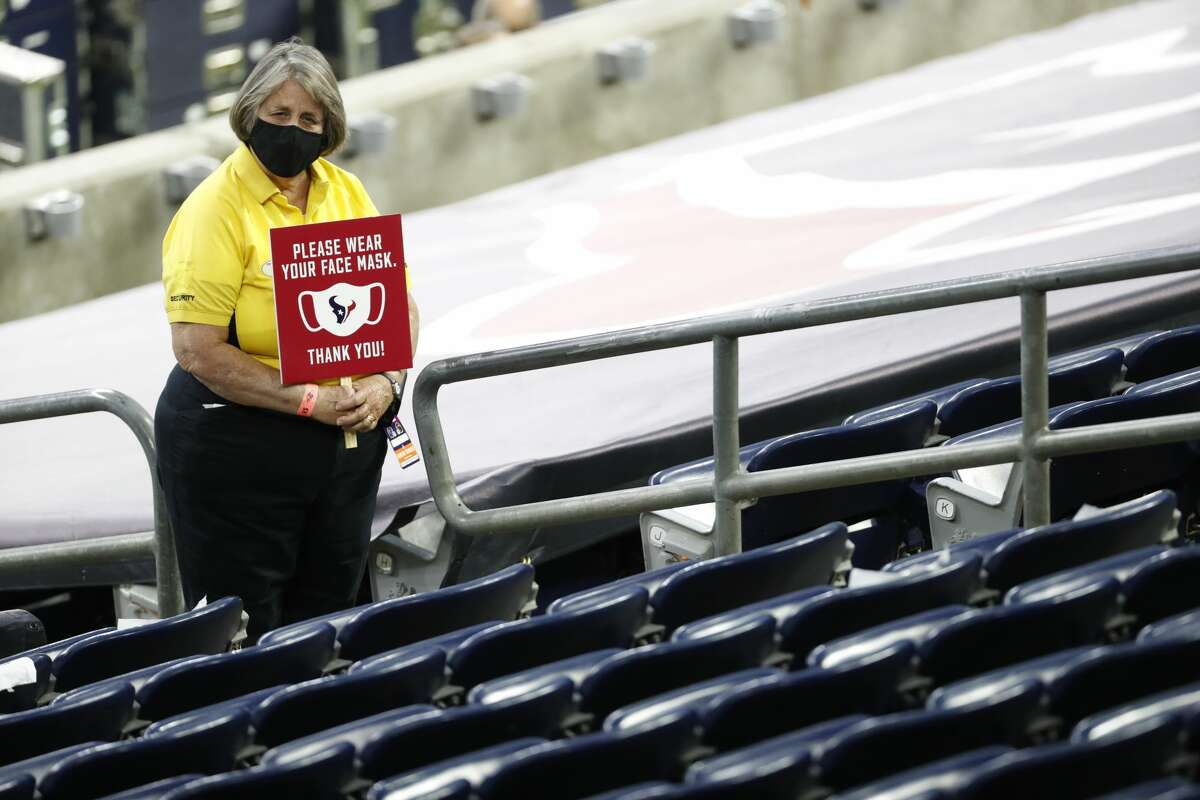 A security guard holds a wear your face mask city before an NFL football game at NRG Stadium on Sunday, Sept. 20, 2020, in Houston.