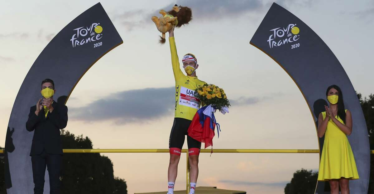 Tour de France winner Slovenia's Tadej Pogacar, wearing the overall leader's yellow jersey, celebrates on the podium after the twenty-first and last stage of the Tour de France cycling race over 122 kilometers (75.8 miles), from Mantes-la-Jolie to Paris, France, Sunday, Sept. 20, 2020. (AP Photo/Thibault Camus)