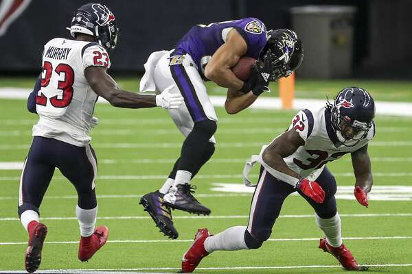 Baltimore Ravens wide receiver Willie Snead (83) is tackled by Houston Texans cornerback Lonnie Johnson (32) and strong safety Eric Murray (23) during the fourth quarter of an NFL football game Sunday, Sept. 20 2020, at NRG Stadium in Houston.