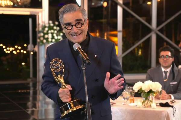 "In this video grab captured on Sept. 20, 2020, courtesy of the Academy of Television Arts & Sciences and ABC Entertainment, Eugene Levy accepts the outstanding lead actor in a comedy series award for ""Schitt's Creek"" as his son and castmate Dan Levy looks on at right during the 72nd Emmy Awards broadcast. (The Television Academy and ABC Entertainment via AP)"