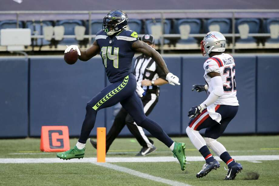 Seattle Seahawks wide receiver DK Metcalf, left, scores a touchdown ahead of New England Patriots free safety Devin McCourty, right, during the first half of an NFL football game, Sunday, Sept. 20, 2020, in Seattle. (AP Photo/John Froschauer) Photo: John Froschauer/AP / Copyright 2020 The Associated Press. All rights reserved.
