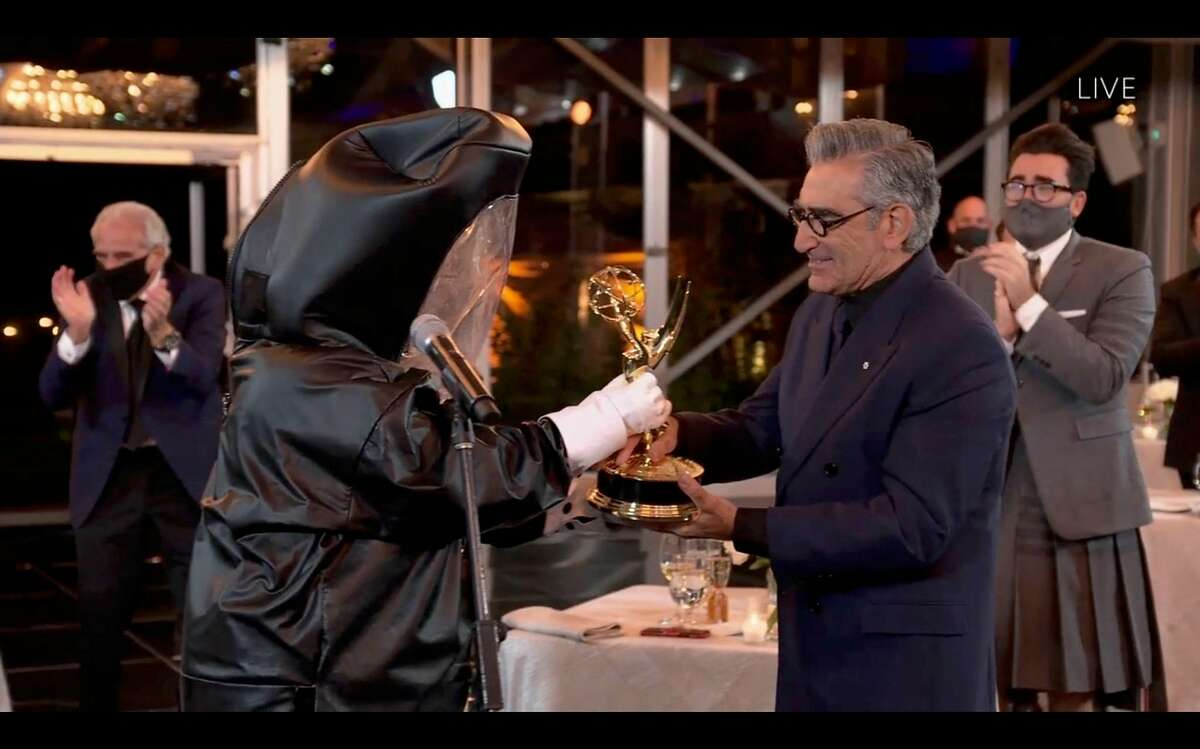 Canadian actor Eugene Levy receives his Emmy while his son actor/director/writer Daniel Levy watches during the 72nd Primetime Emmy Awards ceremony held virtually on September 20, 2020.