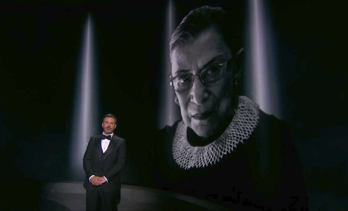 Jimmy Kimmel presents an In Memoriam segment as an image of the late Supreme Court Justice Ruth Bader Ginsburg appears on screen during the 72nd Emmy Awards broadcast.