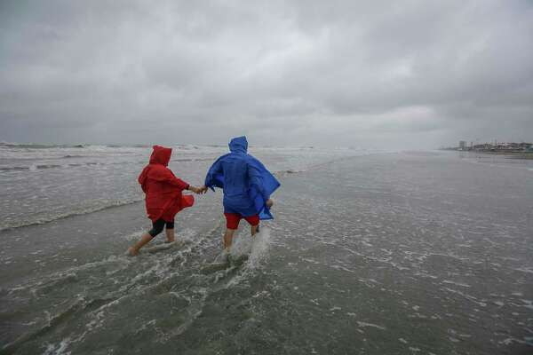 Hugo Villagomez (left) and his girlfriend Faviola Mendoza, both from San Antonio battle the wind and the rain near the 61st Street Pier as Tropical Storm Beta approaches Sunday, Sept. 20, 2020, in Galveston.
