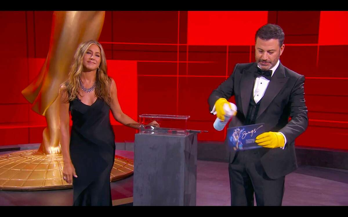 Host Jimmy Kimmel and actress Jennifer Aniston disinfect ballots during the 72nd Primetime Emmy Awards ceremony held virtually on September 20, 2020.
