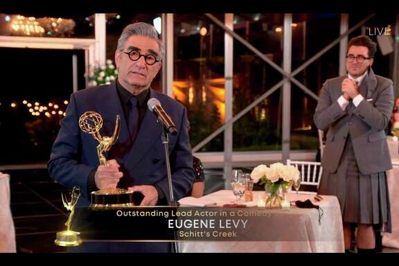"This handout picture released courtesy of Image Group LA / American Broadcasting Companies, Inc. / ABC shows host Canadian actor Eugene Levy speaks after receiving his Emmy while his son actor/director/writer Daniel Levy watches during the 72nd Primetime Emmy Awards ceremony held virtually on September 20, 2020. - Offbeat Canadian hit ""Schitt's Creek"" won the Emmy for outstanding comedy series, capping a major sweep in their categories to open the unusual pandemic-era virtual ceremony honoring the best in television. (Photo by Image Group LA / American Broadcasting Companies, Inc. / ABC / AFP) / RESTRICTED TO EDITORIAL USE - MANDATORY CREDIT ""AFP PHOTO / Image Group LA / American Broadcasting Companies, Inc. / ABC"" - NO MARKETING NO ADVERTISING CAMPAIGNS - DISTRIBUTED AS A SERVICE TO CLIENTS --- NO ARCHIVE --- / TABLOIDS OUT; NO BOOK PUBLISHING WITHOUT PRIOR APPROVAL. NO ARCHIVE. NO RESALE."