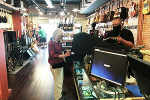 ON THE COVER: Mojo's Music's full-time consultant, Turk Myers, helps regular customer Shar Joyce as she picks up a new guitar case at the Edwardsville specialty retailer at 144 N. Main St., celebrating its 20th anniversary. Former owner Bob Moggio, of Glen Carbon, established Mojo's on Oct. 1, 2000.   (Jill Moon|The Edge)