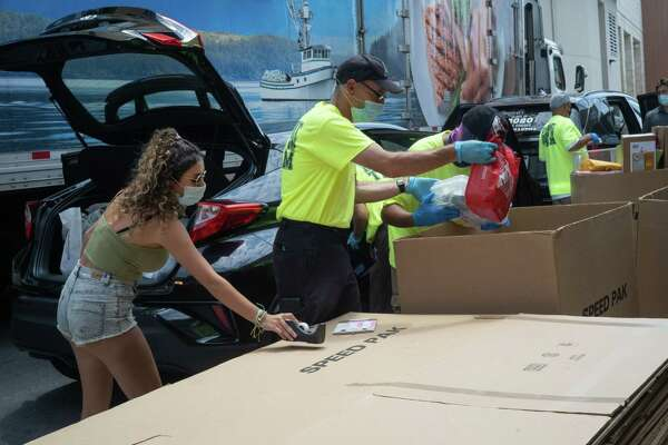 Movers wearing protective masks help students move into freshman housing at South Campus Plaza on the San Diego State University campus in San Diego, Calif., on Aug. 21, 2020.