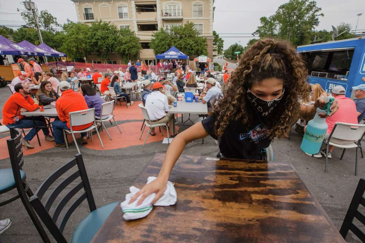 A server cleans a table in an outdoor area at a restaurant during Clemson University's first home football game in Clemson, S.C., on Sept. 19, 2020.