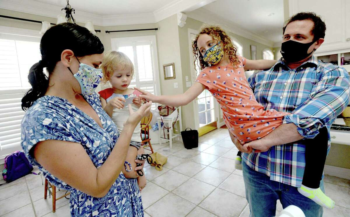 Dr. Nikki Hancock holds daughter Addy, 2, as husband Cliff holds Lucy, 7, at home after a day of work caring for COVID-19 patients at Baptist Hospital. The family's normal after-work routine has shifted amid the virus and her work as a frontline healthcare provider to some of Southeast Texas' sickest patients. Dr. Hancock no lonnger walks through the door to hug annd kiss her children. She has a decontamination room set up in her garage, where after pulling in, she disrobes, putting her clothinng from the day in a bucket to be washed at week's end, scrubbs with sanitizer, then showers. After, she joinns her husband, Dr. Cliff Hancock and their three children and shifts from coronavirus caregiver to wife and mother. Photo taken Tuesday, August 18, 2020 Kim Brent/The Enterprise