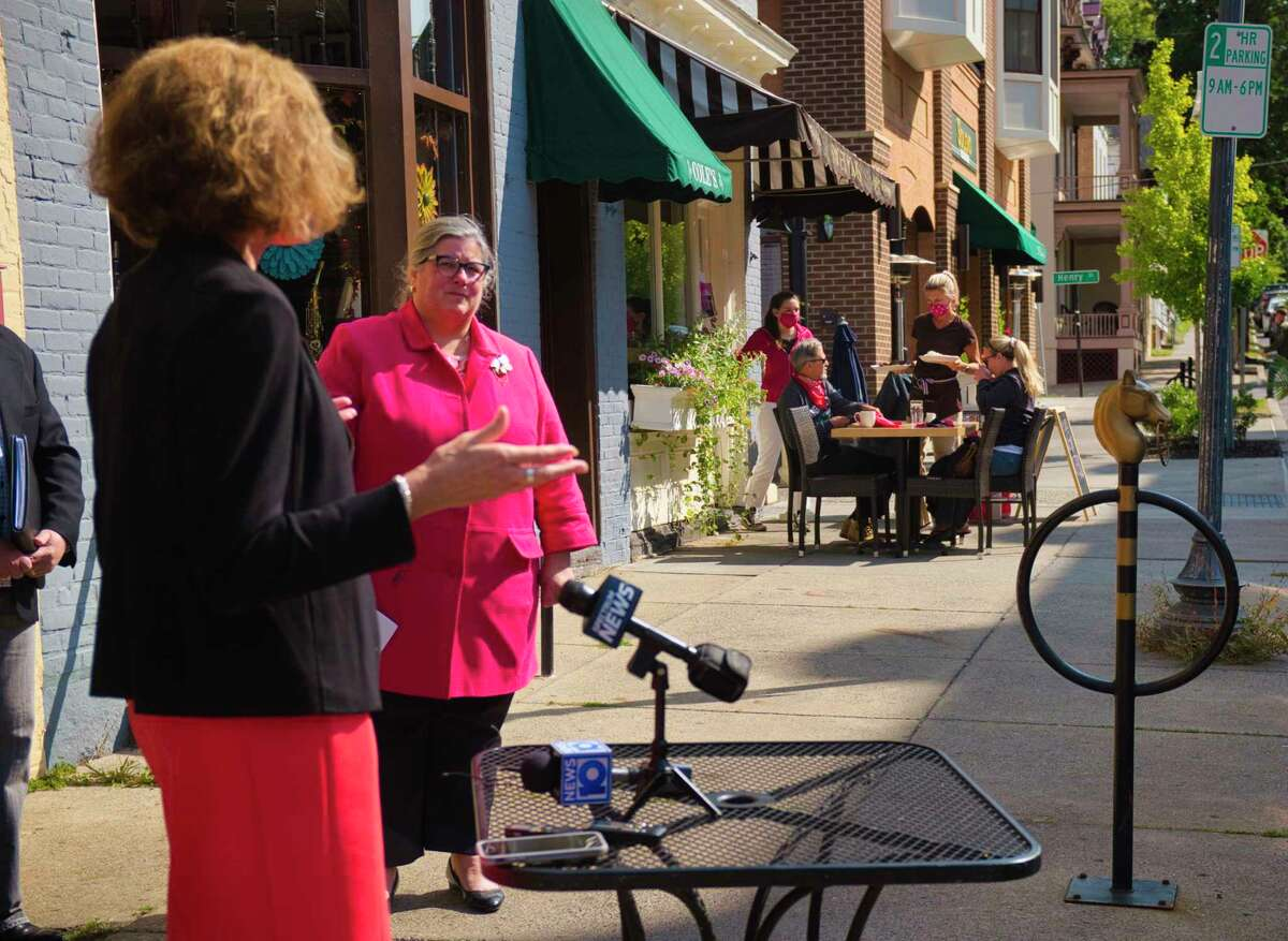 People dine on the sidewalk outside of Sweet Mimi's as Assemblywoman Patricia Fahy speaks at a press conference held outside of Hattie's on Monday, Sept. 21, 2020, in Saratoga Springs, N.Y. Assemblywoman Carrie Woerner along with Assemblywoman Patricia Fahy, and Assemblyman John McDonald III, held the press event to urged the state to immediately increase indoor dining capacity to 75%, provided their county?•s infection rate remains at or below 1%. (Paul Buckowski/Times Union)