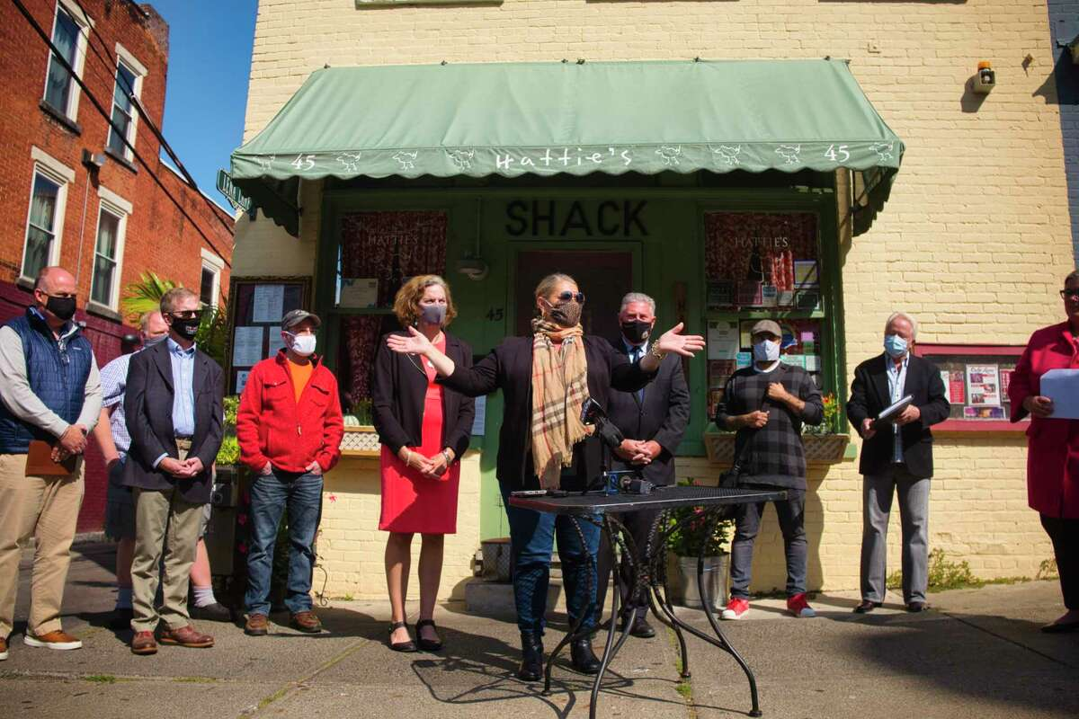 Beth Alexander, owner of Hattie's, surrounded by elected officials, restaurant owners, and city officials, speaks at a press conference held outside of Hattie's on Monday, Sept. 21, 2020, in Saratoga Springs, N.Y. Assemblywoman Carrie Woerner along with Assemblywoman Patricia Fahy, and Assemblyman John McDonald III, held the press event to urged the state to immediately increase indoor dining capacity to 75%, provided their county?•s infection rate remains at or below 1%. (Paul Buckowski/Times Union)